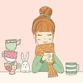 Cute girl in sweater drinks cup of tea