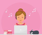 Cute girl with headphones listening to music and working on a laptop. Chat, dating, education, blogging and search for information on the network.