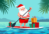 Cute Santa Claus in shorts and t-shirt on a stand up paddle board with gifts, against tropical ocean background with palm trees. Warm weather Christmas celebration, warm climate holiday vacation theme