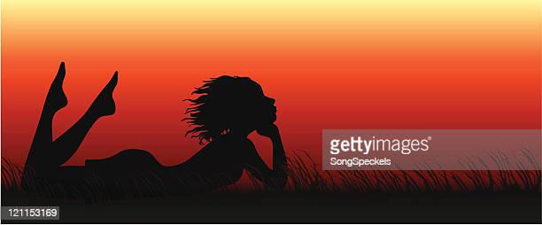 Daydreaming girl laying in the grass during Sunset