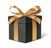 Decorative black gift box with golden bow isolated on white.