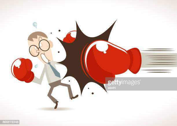 Defeated businessman boxer being hit by a huge boxing glove