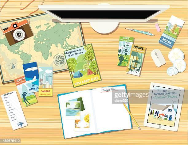 Schreibtisch mit Objekten für einen Urlaub planen oder eine Reise
