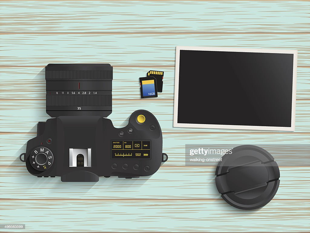 Digital camera, memory card and photo on wood table
