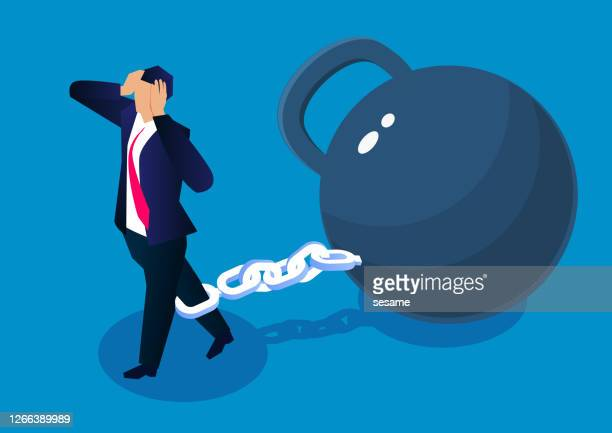 distressed businessman tied with iron chain drags huge iron ball to walk - debt stock illustrations
