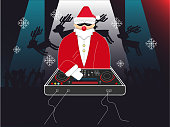 Dj Santa with EDM mixing and producing machine instrument under colorful club light in night club for Christmas time