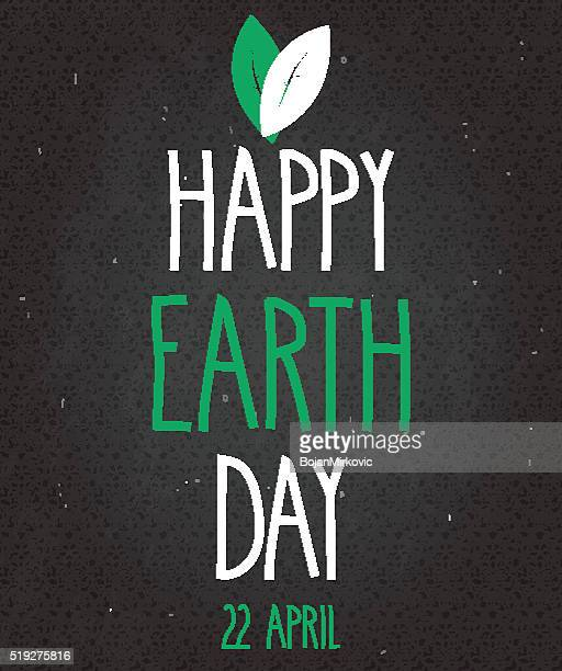earth day poster on black chalkboard. handwritten text with leafs - earth day stock illustrations