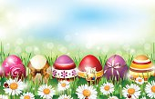 Easter background with colorful eggs lying in fresh grass