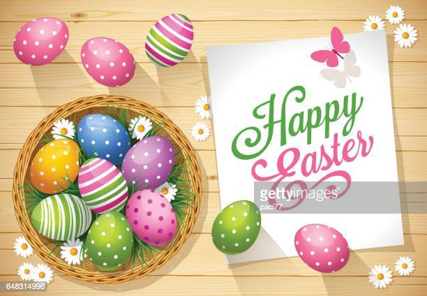 easter eggs with greeting card on a wooden background - easter stock illustrations
