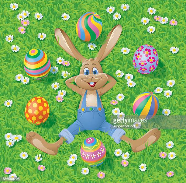 easterbunny with eastereggs on grass - easter bunny stock illustrations