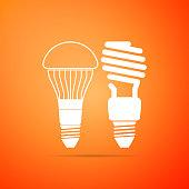 Economical LED illuminated lightbulb and fluorescent light bulb icon isolated on orange background. Save energy lamp. Flat design. Vector Illustration