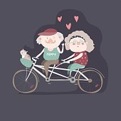 Elderly couple riding a bicycle tandem