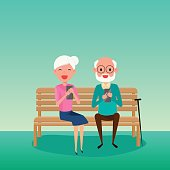 Elderly couple.Happy Grandparents day. Grandparents using smart phone sitting on a bench in the park.