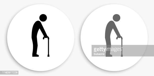 elderly man holding cane black and white round icon - walking cane stock illustrations