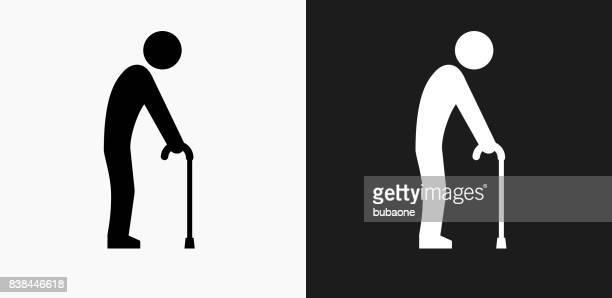 elderly man holding cane icon on black and white vector backgrounds - walking cane stock illustrations
