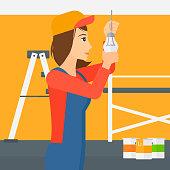 Electrician twisting light bulb