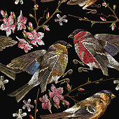 Embroidery birds and blossoming cherry seamless pattern. Classical embroidery bullfinch and titmouse on branch blossoming sakura. Spring fashion pattern, template for design of clothes, t-shirt design
