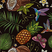 Embroidery humming bird, palm tree leaves, pineapple, buterflly, coconut tropical seamless pattern. Template for design of clothes. Fashionable embroidery tropical butterfly, summer background