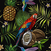 Embroidery parrot, humming bird, palm tree leaves, pineapple, coconut tropical seamless pattern. Fashionable embroidery tropical summer background. Template for design of clothes