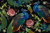 Embroidery peacocks and flowers peonies seamless pattern. Classical fashionable embroidery beautiful peacocks. Fashionable template for design of clothes. Tails of peacocks and roses