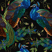 Embroidery peacocks tropical birds and flowers seamless pattern. Classical fashionable embroidery beautiful peacocks. Fashionable template for design of clothes. Tails of peacocks art.