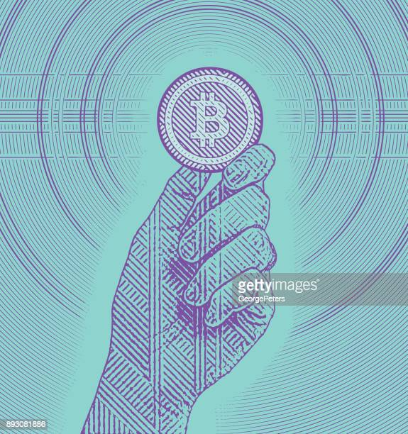 engraving illustration of a hand holding a bitcoin - cryptocurrency stock illustrations