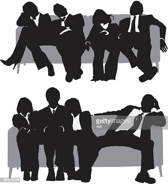 Exhausted business executives sitting on sofa