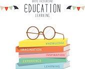 Eyeglasses on top stack books.