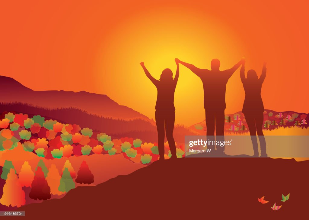 Family standing on top of fall mountain with raised hands.