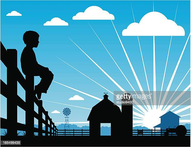Farm boy silhouetted sitting on a fence