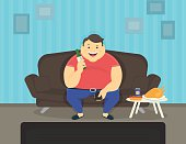 Fat man sitting at home on the sofa watching tv