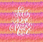 Feliz Dia De La Madre hand lettering.Translation from Spanish Happy Mothers Day.Calligraphy on leaves design background.