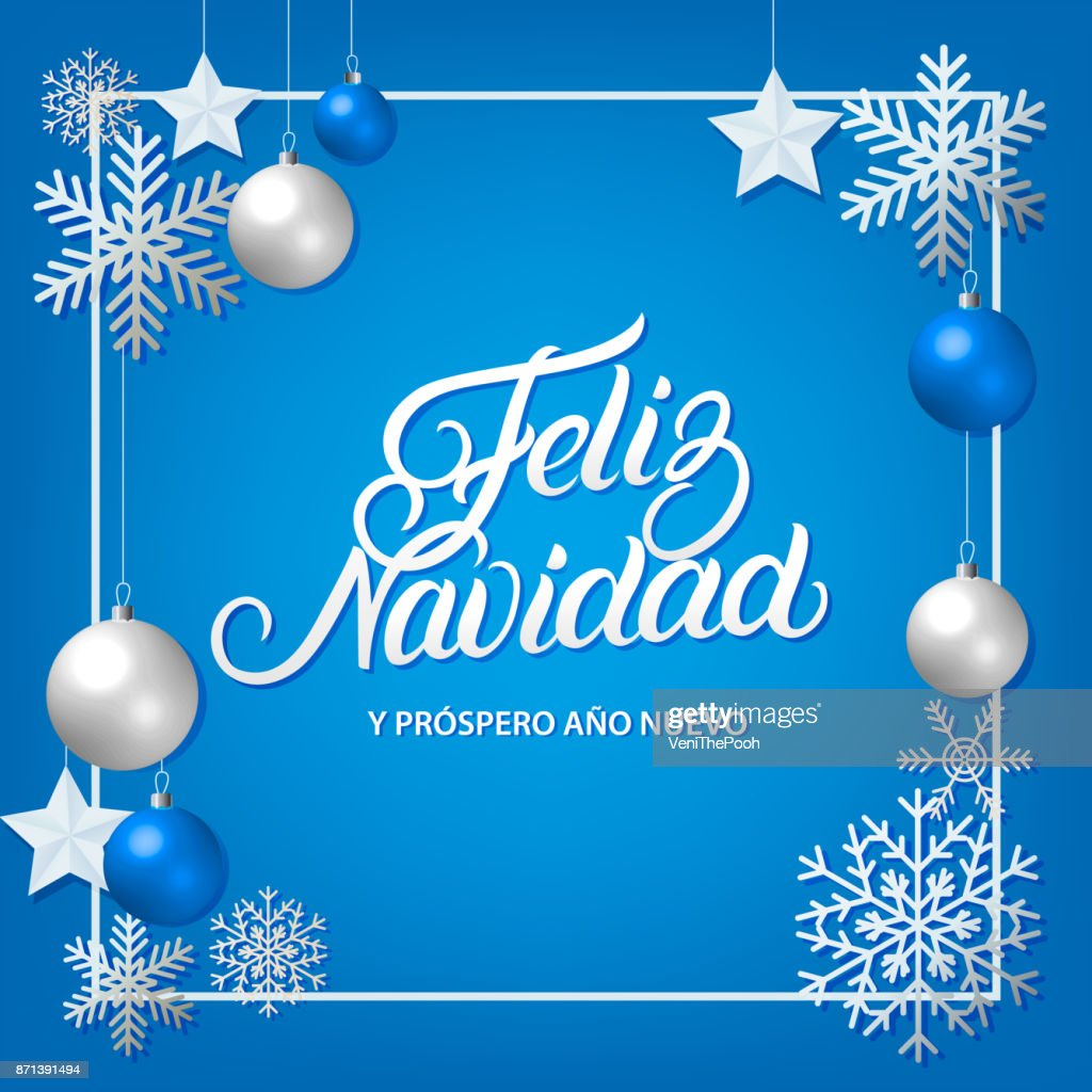 Feliz Navidad hand written lettering with silver decoration ornament.