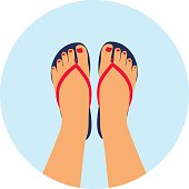 female feet with a pedicure in the summer flip-flops.