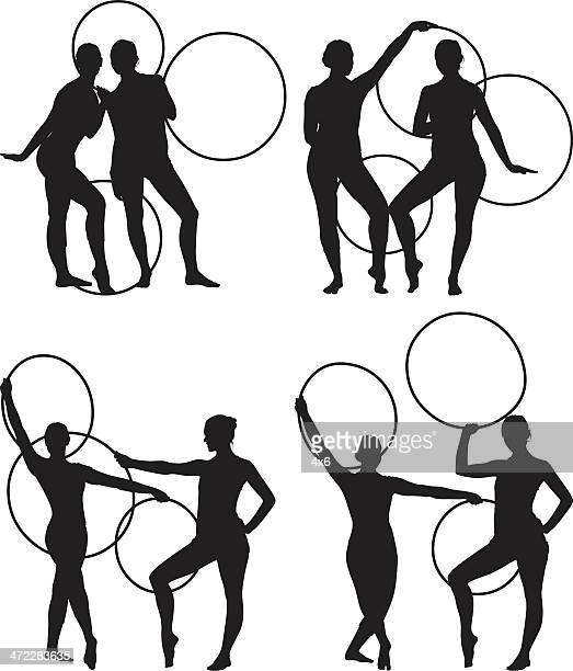 female gymnasts dancing with hoops - contortionist stock illustrations