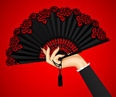 Female hand with open black vintage fan isolated on red light background