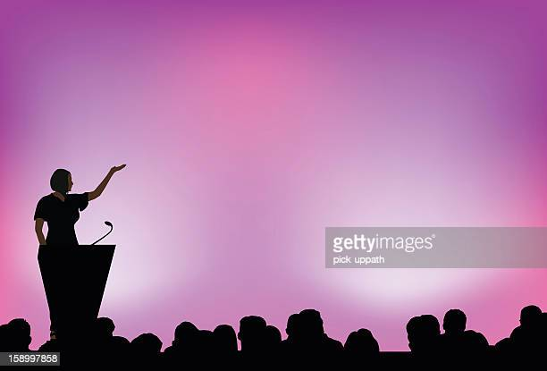 A female presenting to an audience in front of purple lights