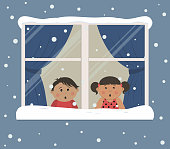 First snow. Children looks at the snow through the window
