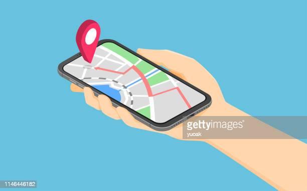flache 3d isometrische hand hält smartphone mit punkt auf der karte anwendung - gps stock-grafiken, -clipart, -cartoons und -symbole
