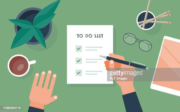 flat vector illustration of person checking to do list at desk - to do list stock illustrations