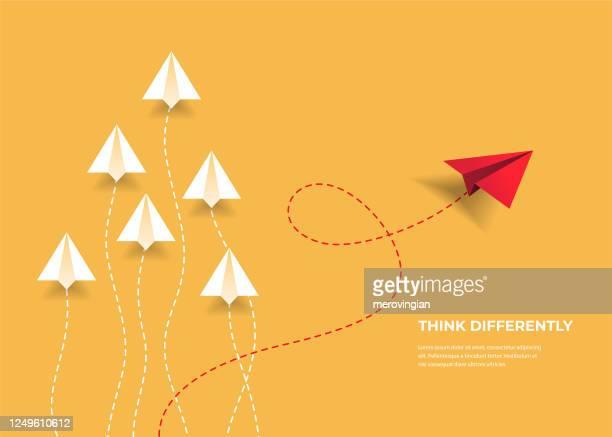 fliegende papierflugzeuge. anders denken, führung, trends, kreative lösung und einzigartiges wegkonzept. seien sie anders. - individualität stock-grafiken, -clipart, -cartoons und -symbole