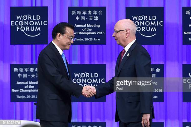 Founder and executive chairman of the WEF Klaus Schwab shakes hands with Chinese Premier Li Keqiang during the World Economic Forum on June 27 2016...