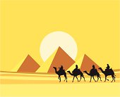 Four camels with riders silhouetted against the Pyramids