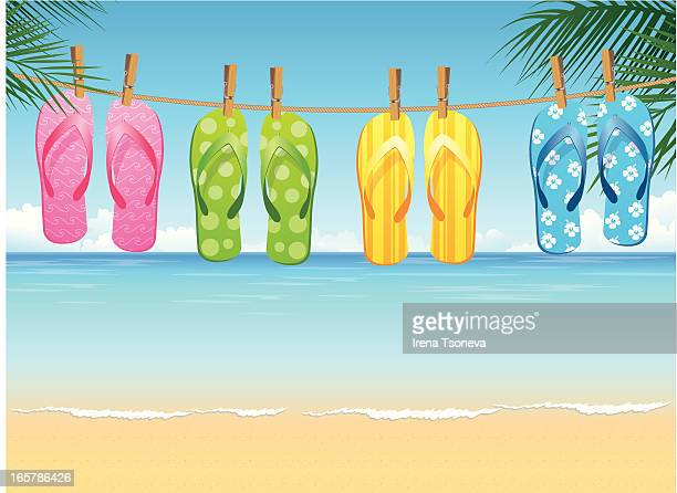 Four colorful pairs of flip flops hanging on tropical beach