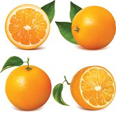Four fresh oranges with leaves, two sliced