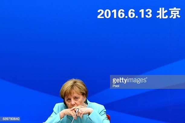 German Chancellor Angela Merkel listens as she attends SinoGerman Economic Advisory with Chinese Premier Li Keqiang at the Great Hall of the People...