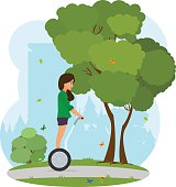 Girl in a city park rides a Segway.