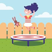 Girl jumping on a trampoline at the backyard