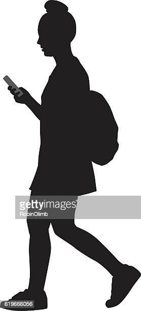 Girl Walking And Looking At Smart Phone