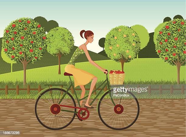 女の子、自転車とリンゴの田園地帯